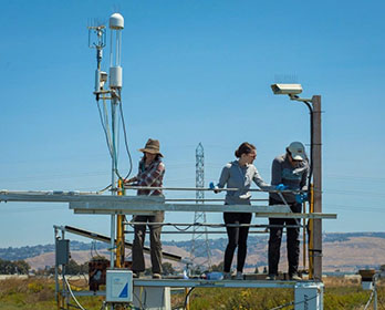 Three female researchers install equipment on a monitoring tower in the Sacramento-San Joaquin Delta.